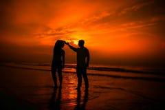 Pares que ejercitan en la playa Imágenes de archivo libres de regalías