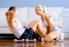 Pares que ejercitan en suelo de la sala de estar Fotografía de archivo libre de regalías
