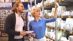 Pares que eligen artículos del hogar en minorista Consumerismo, compras, forma de vida almacen de metraje de vídeo