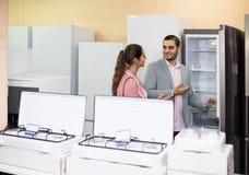 Pares que eligen el nuevo refrigerador en hipermercado fotografía de archivo