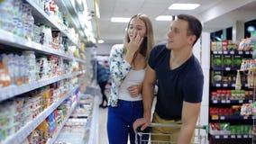 Pares que empujan el carro de la compra en supermercado almacen de metraje de vídeo