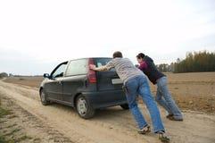 Pares que empurram um carro Fotografia de Stock