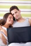Pares que encontram-se na cama com sorriso do portátil imagens de stock royalty free