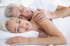 Pares que encontram-se na cama que sorri junto Fotografia de Stock
