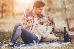 Pares que encontram-se na grama e no vinho da bebida no parque imagem de stock royalty free