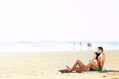Pares que encontram-se na praia Fotografia de Stock Royalty Free