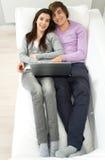 Pares que encontram-se no sofá Fotografia de Stock Royalty Free