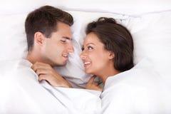 Pares que encontram-se no sorriso da cama Fotos de Stock Royalty Free
