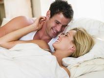 Pares que encontram-se no sorriso da cama foto de stock royalty free