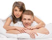 Pares que encontram-se no sorriso da cama Foto de Stock