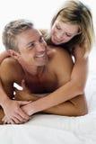 Pares que encontram-se no sorriso da cama imagem de stock royalty free