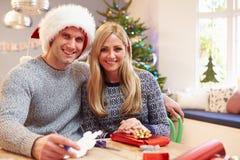 Pares que envolvem presentes do Natal em casa Imagens de Stock Royalty Free