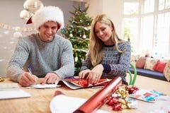 Pares que envuelven los regalos de la Navidad en casa Imágenes de archivo libres de regalías