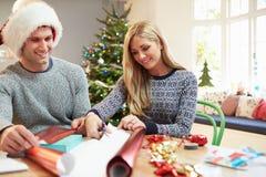 Pares que envuelven los regalos de la Navidad en casa Imagen de archivo