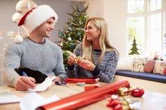 Pares que envuelven los regalos de la Navidad en casa Imagenes de archivo