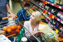 Pares que escolhem o queijo na loja Imagem de Stock Royalty Free