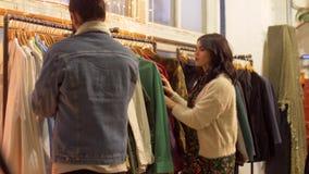 Pares que escolhem a roupa na loja de roupa do vintage filme