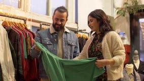 Pares que escolhem a roupa na loja de roupa do vintage vídeos de arquivo