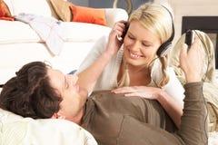 Pares que escuchan el jugador MP3 que pone en la manta Imagen de archivo libre de regalías