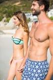 Pares que estão na costa na praia Fotos de Stock Royalty Free