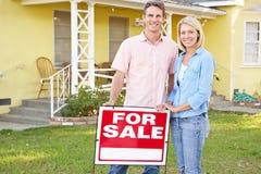 Pares que estão perto para o sinal da venda fora da casa Fotografia de Stock Royalty Free