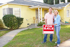 Pares que estão perto para o sinal da venda fora da casa Foto de Stock