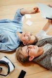 Pares que estudian mientras que miente en piso en casa Fotos de archivo libres de regalías