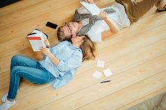 Pares que estudian mientras que miente en piso en casa Imágenes de archivo libres de regalías