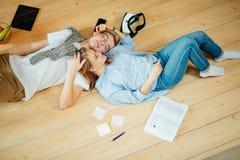 Pares que estudian mientras que miente en piso en casa Fotografía de archivo