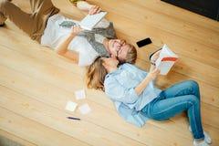 Pares que estudian mientras que miente en piso en casa Imagen de archivo