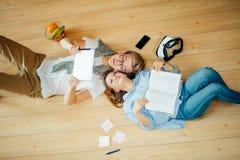 Pares que estudian mientras que miente en piso en casa Foto de archivo libre de regalías
