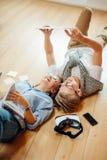 Pares que estudian mientras que miente en piso en casa Imagen de archivo libre de regalías
