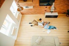 Pares que estudian mientras que miente en piso en casa Imagenes de archivo