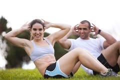 Pares que exercitam no parque Fotografia de Stock