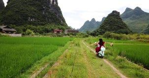 Pares que exploram vilas de Yangshuo no velomotor video estoque