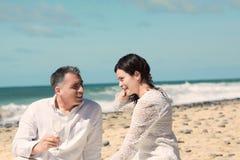 Pares que falam e que sentam-se na praia Imagem de Stock