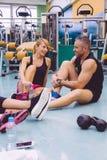 Pares que falam no fitness center após a formação Fotografia de Stock Royalty Free