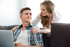 Pares que fazem compras no Internet usando o portátil e o cartão de crédito Fotografia de Stock
