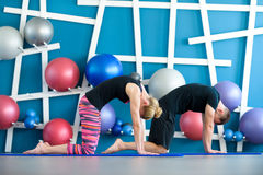 Pares que fazem a ioga em um estúdio Os jovens na classe da ioga no gato levantam Conceito do grupo da ioga foto de stock royalty free