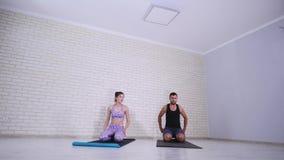 Pares que fazem a ioga junto no estúdio fotos de stock
