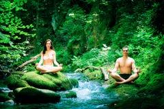Pares que fazem a ioga pelo rio Imagem de Stock