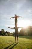 Pares que fazem o exercício acrobático da ioga no parque Imagem de Stock Royalty Free