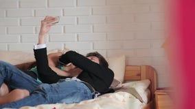 Pares que fazem o selfie que encontra-se na cama video estoque