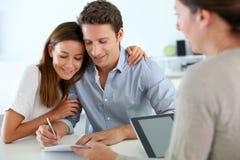 Pares que firman el contrato inmobiliario Fotografía de archivo libre de regalías