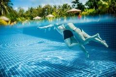 Pares que flotan en la piscina el día de fiesta Foto de archivo libre de regalías