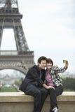 Pares que fotografían en Front Of Eiffel Tower Imágenes de archivo libres de regalías