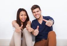 Pares que gesticulam os polegares acima em casa Fotografia de Stock Royalty Free