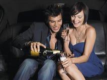 Pares que gozan de Champagne In Limousine Fotos de archivo