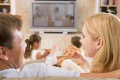 Pares que gozan de la pizza delante de la TV Imagen de archivo libre de regalías