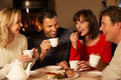 Pares que gozan de té y de la torta junto Fotos de archivo libres de regalías